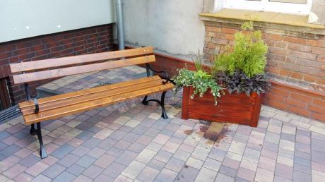 Żeliwna ławka ogrodowa ustawiona na tarasie z kostki