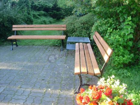 Żeliwne ławki ogrodowe ustawione na tarasie z kostki