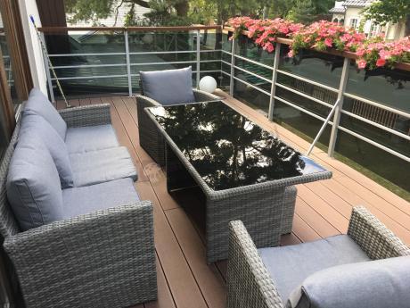 Zestaw mebli na taras technorattan na balkonie ozdobionym kwiatami