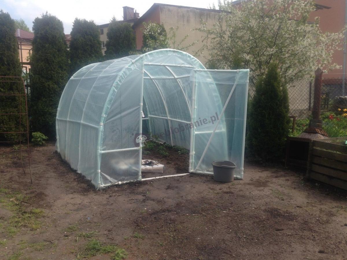 Mały tunel foliowy na działkę ze świeżo zasadzonymi roślinami