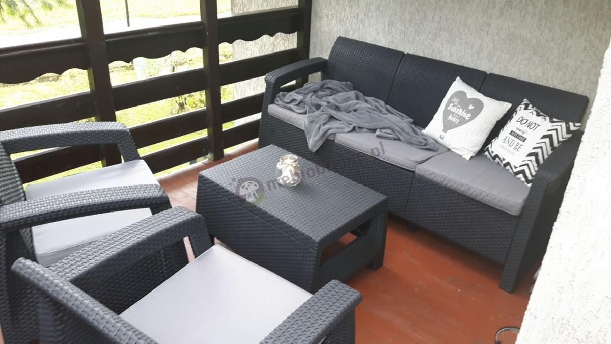 Meble Curver Corfu z sofą trzyosobową używane na niewielkim balkonie
