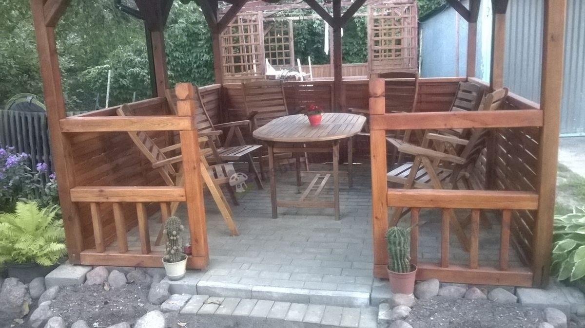 Meble drewniane ogrodowe w uroczej drewnianej altanie