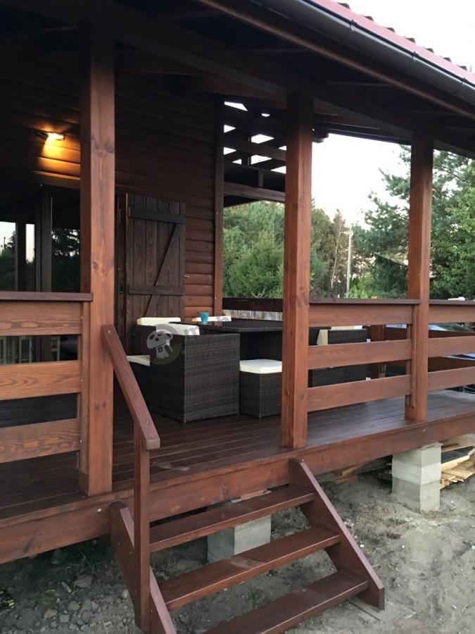 Meble na drewnianym tarasie domku letniskowego Cubioso Brown