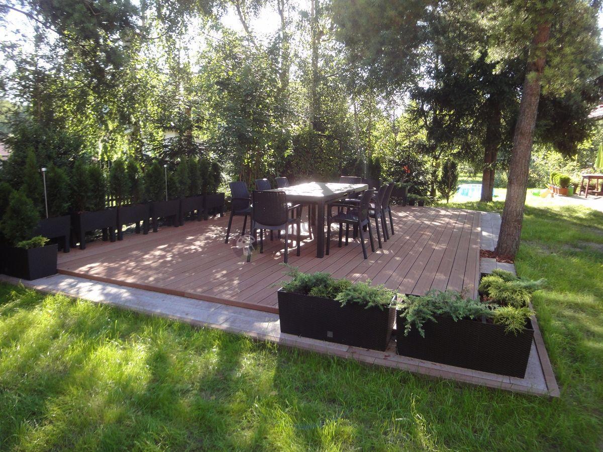 Meble ogrodowe na dużym tarasie ozdobionym roślinami
