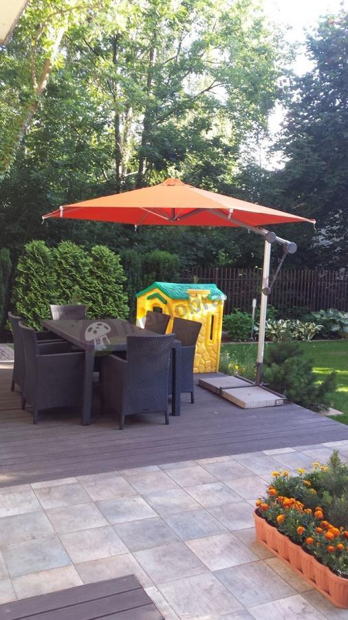 Meble ogrodowe na tarasie osłonięte parasolem