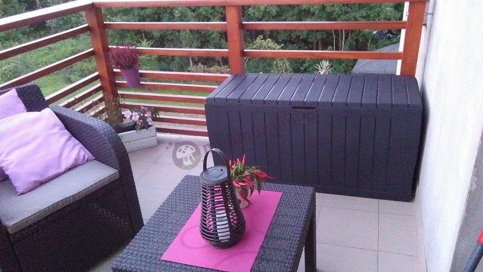 Meble ogrodowe ze skrzynią na poduszki w uroczej aranżacji