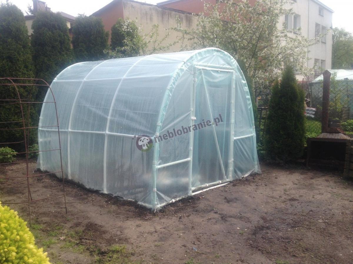 Nieduży tunel foliowy w ogrodzie otoczony przez rośliny