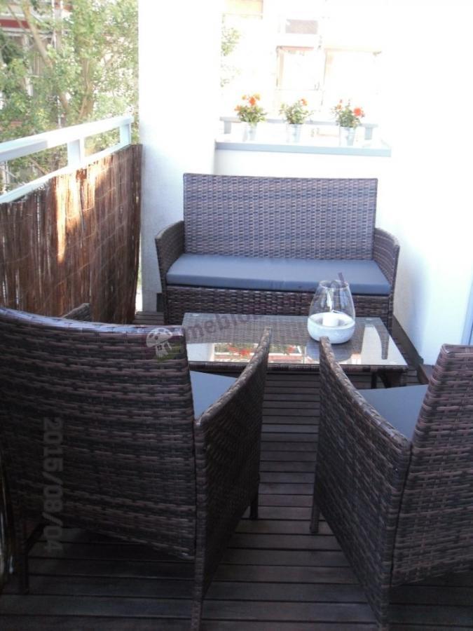 Nowoczesne meble technoratanowe z poduszkami szarymi na balkonie