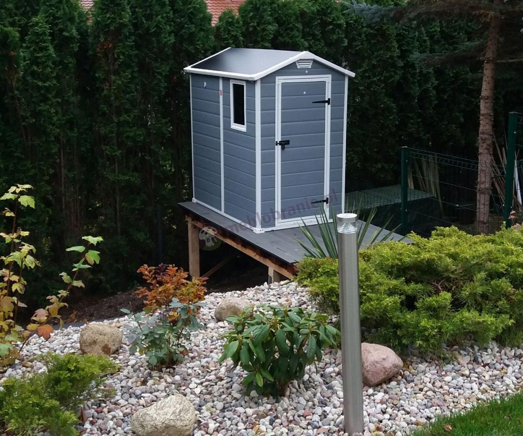 Ogrodowy domek narzędziowy Keter Manor ustawiony za rabatą ogrodową