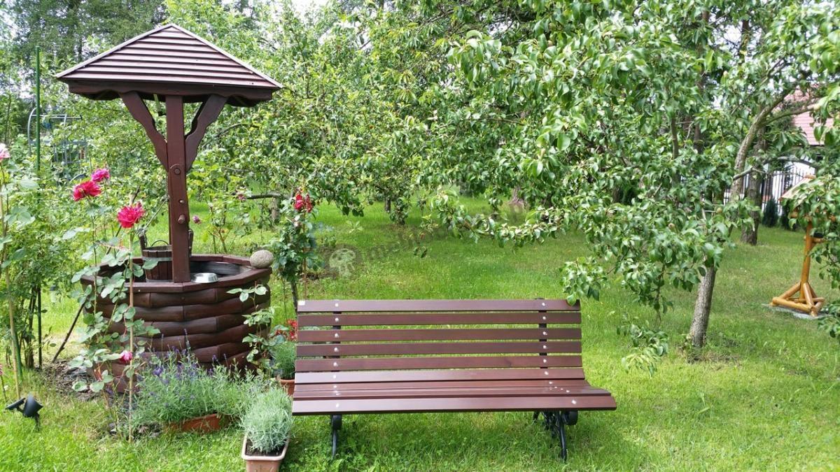 Ozdobna ławeczka ogrodowa na 11 desek pośród zielonej flory