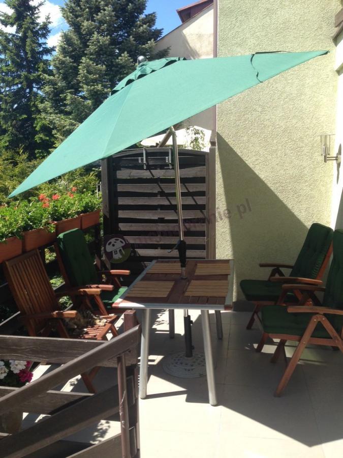 Parasol ogrodowy Sunline używany jako osłona tarasu
