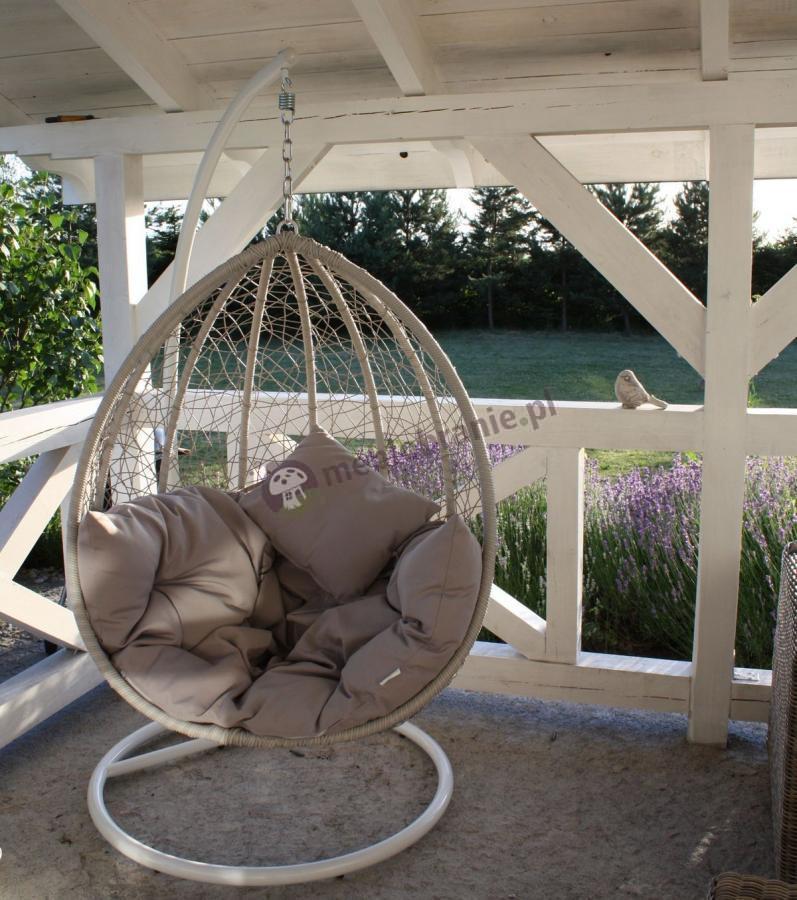 Piękny biały fotel wiszący na łańcuchu na tarasie Dondolo