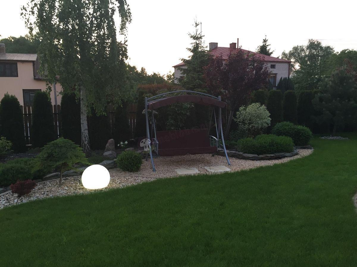 Rozkładana huśtawka ogrodowa w uroczym ogrodzie