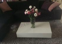 Biały stolik kawowy ozdobiony świeżymi kwiatami