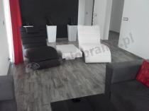 Biały stolik kawowy wysoki połysk między nowoczesnymi fotelami