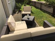 Brązowe meble ogrodowe ustawione w niewielkim ogródku