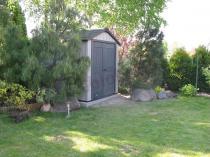 Domek ogrodowy Keter Oakland ustawiony pośród drzew