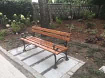 Drewniana ławka parkowa z ładną grządką kwiatową w tle