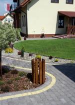 Drewniany kosz na śmieci w eleganckim ogrodzie