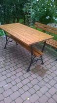 Drewniany stół ogrodowy z ławkami ustawiony w sąsiedztwie roślin