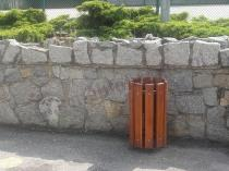 Kosz na śmieci okrągły na tle kamienia w parku
