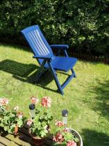 Krzesło ogrodowe składane plastikowe ustawione przy żywopłocie
