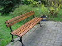 Ławka ogrodowa ustawiona w pełnym zieleni ogrodzie