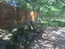 Ławka żeliwna do ogrodu ustawiona pod drzewem