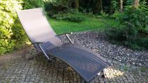 Leżak ogrodowy aluminiowy Relax ustawiony wśród roślin