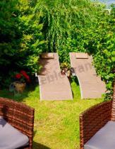 Leżak ogrodowy ustawiony w tle technorattanowego kompletu