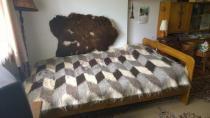 Łóżko drewniane do sypialni Saranda przykryte wełnianą narzutą
