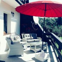 Meble balkonowe z technorattanu białe pod czerwonym parasolem