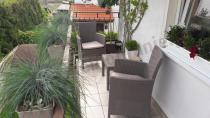 Meble na balkon rattan efekt otoczone bujną roślinnością