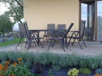 Meble ogrodowe z aluminium na tarasie otoczonym kwiatami