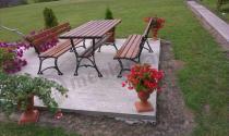 Meble żeliwne drewniane uzupełnione kwiatową kompozycją