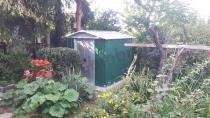 Metalowy domek narzędziowy Yardmaster w pełnym zieleni ogrodzie