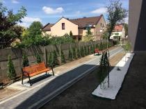 Nowoczesna ławka ogrodowa drewniana ustawiona przy bloku