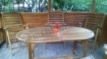Owalny stół w altanie z drewnianymi krzesłami