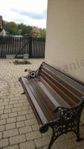Ozdobna ławka ogrodowa drewniana ustawiona na chodniku