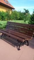 Ozdobna ławka ogrodowa z zielenią w tle