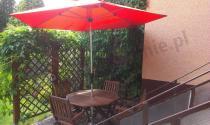 Parasol przeciwsłoneczny używany, by uchronić przed słońcem drewniane meble ogrodowe