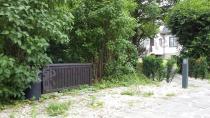 Skrzynia ogrodowa z siedziskiem ustawiona pośród drzew i krzewów