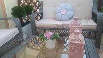 Sofa z technorattanu ozdobiona uroczą poduszeczką-kwiatkiem