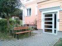 Stalowa ławka parkowa przed wejściem do klatki schodowej