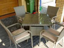 Stół i krzesła technorattan z dodatkowymi poduszkami ustawione przy domu