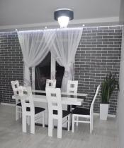 Stół nowoczesny biały z czarnymi detalami w salonie