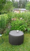 Stolik ze skrzynią Circa ustawiony pośród kwiatów