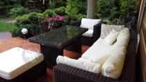 Technorattanowe meble ogrodowe z widokiem na piękny ogród