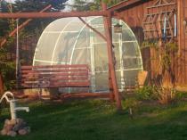 Tunel ogrodowy 2x2,2 m tworzący tło dla drewnianej huśtawki