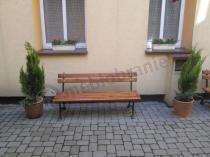 Ustawiona między iglakami żeliwna ławka ogrodowa